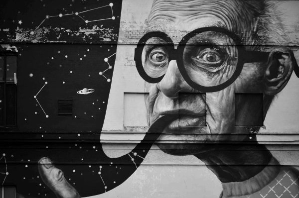 Kaunas streeet art - woman with glasses smoking a pipe becomes the solar system
